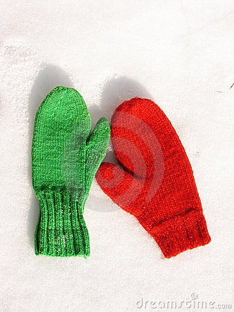 Red and green mittens on snow.