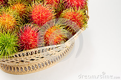 Red and green rambutan in basket.
