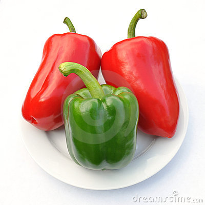 Red and green sweet pepper on white plate