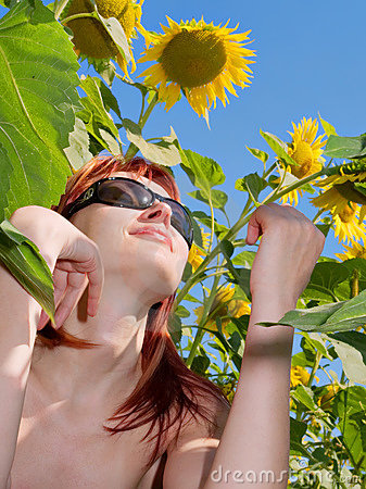 Red-hair girl enjoys sun sitting under sunflowers