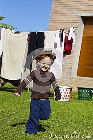 Red haired boy running in garden