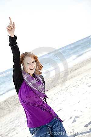 Red-haired girl with headphone on the beach.