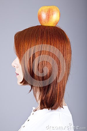 Red-haired girl keep apple on her head.