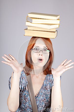 Red-haired girl keep books on her head.