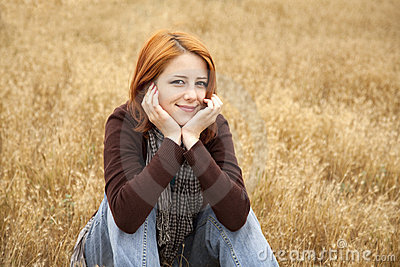 Red-haired girl sitting at yellow autumn grass.