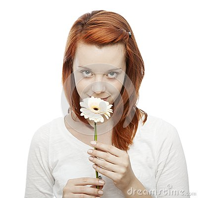 Red haired girl smelling on a flower