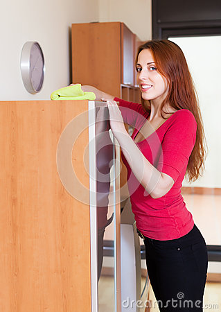 Red-haired girl wiping the dust from  furniture