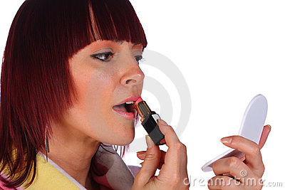 Red-haired woman applying lipstick, isolated