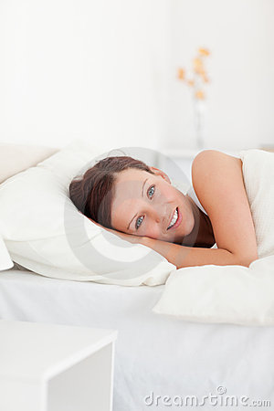 Red-haired woman lying in bed smiling into camera