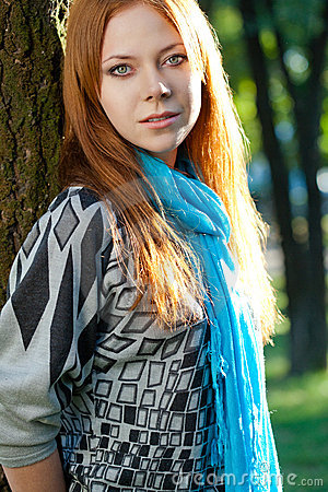 Red-haired woman near tree