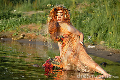 Red-haired woman sitting in water.