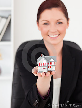 Red-haired woman in suit holding a miniature hous