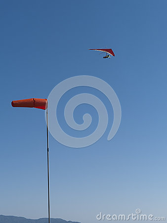 Red hang glider above with wind cone