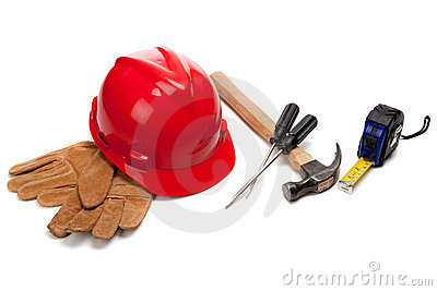 A red hard hat and leather work gloves with tools