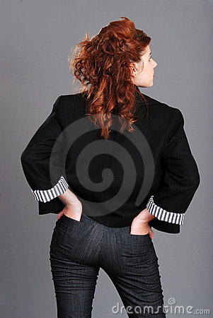 Red head woman with hands in back pockets