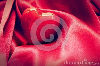 Red heart in satin cloth. Love background