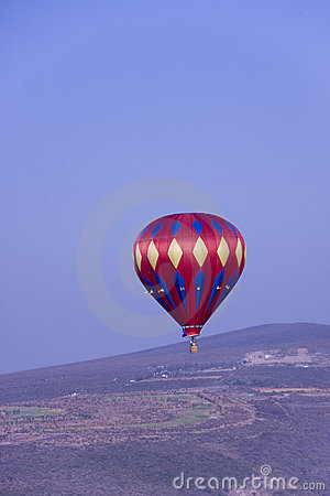 Red hot air balloon flying in mountains