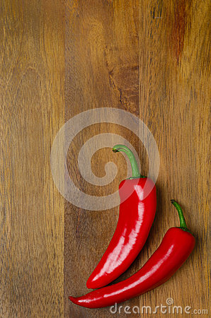 Red hot chili peppers on a wooden background and space for text