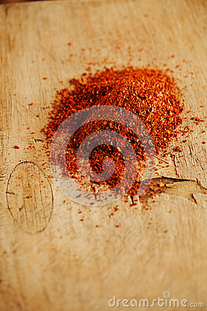 Red hot chillies pepper  flakes  on wooden board  background