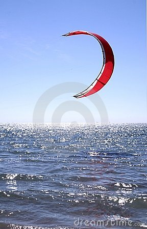 Red Kite Surfer Sail against a blue sky hanging just above the surf. : Dreamstime