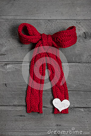 Red knitted bow with white heart on wooden background for christ