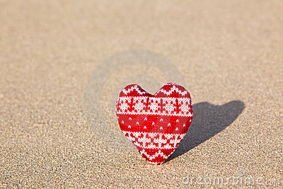 Red knitted heart on sea sand
