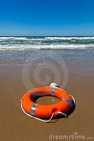 Red lifebuoy lying on the sand on the beach