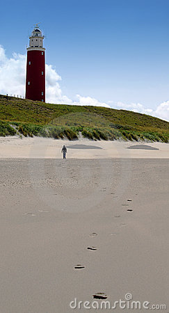 Red lighthouse with footsteps on the beach