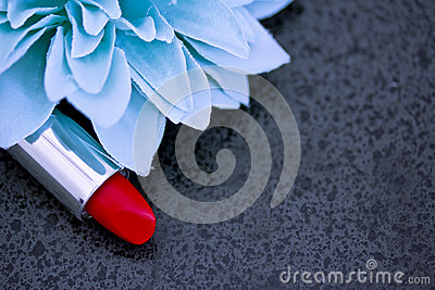 Red lipstick and blue flower petals on black