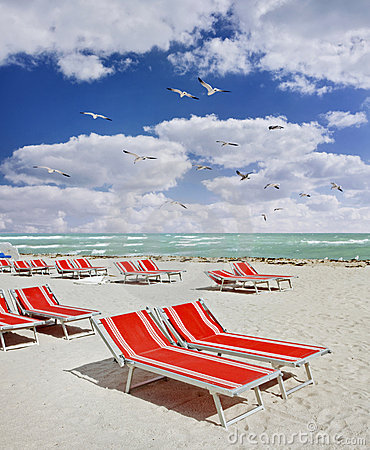 Red lounge chairs on a tropical beach