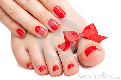 Red manicure and pedicure with a bow. isolated