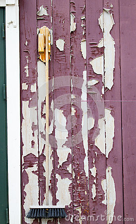Red Paint Peeling off Wooden Planks with Hanging Broom