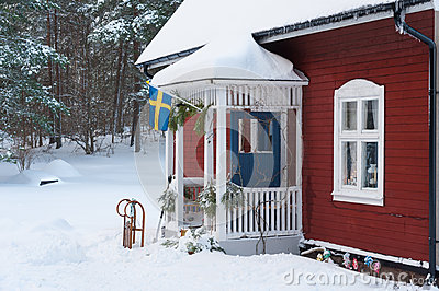 Red painted Swedish wooden house in a wintry landscape