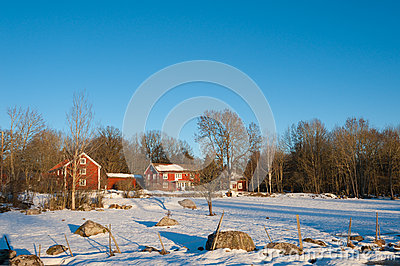 Red painted Swedish wooden houses in a wintry landscape