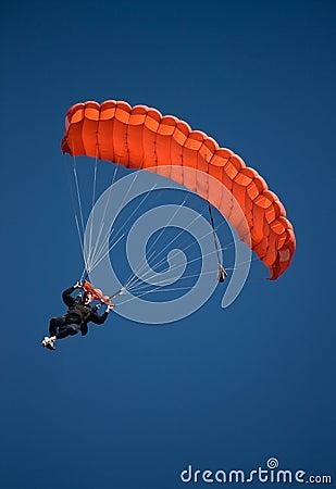 Red parachute against blue sky