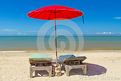 Red parasol with deckchair on tropical beach