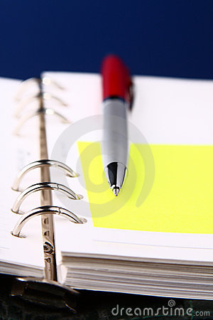 Red pen on an organizer with a selective focus