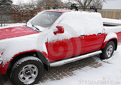 Red pickup with snow in driveway