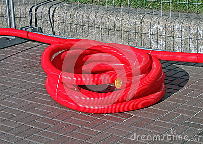 Red plastic cable bulk on the street,
