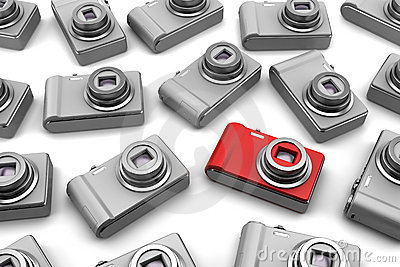 Red point and shoot photo camera among gray