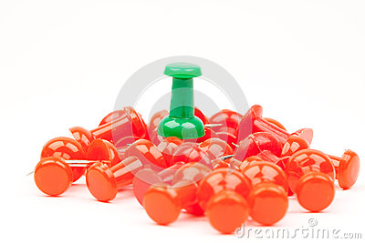 Red push pins with a green push pin standing out