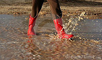 Red rain boots in puddle