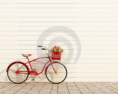 Red retro bicycle with basket and flowers in front of the white wall, background Stock Photo