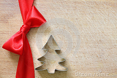 Red ribbon and bow on vintage cutting board christmas background