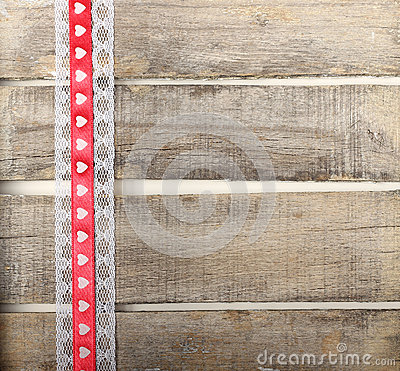 Red ribbon of hearts on old wooden background