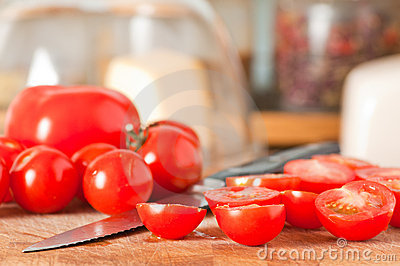 Red ripe cut cherry tomatoes on cutting board