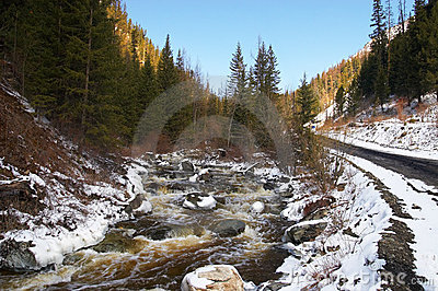 Red river, white ice and green firs.