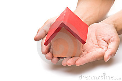 Red roofed house in human hand