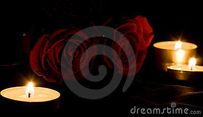 Red rose and candles in the darkness