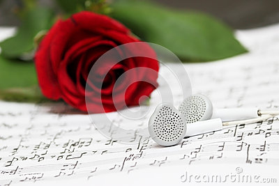 Red rose, earphones, piano sheet music